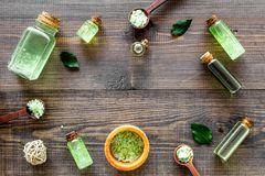 Organic cosmetics with tea tree oil and spa salt on dark wooden background top view copyspace Royalty Free Stock Photography
