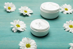 Organic cream in containers and chamomiles on blue wooden table Stock Photos