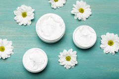 Organic cream in containers and chamomiles on blue wooden table Stock Image