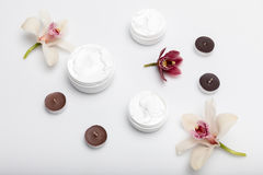 Organic cream in containers with orchids and candles isolated on white Stock Image