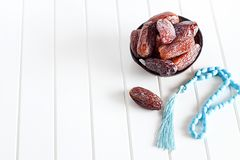 Organic Dates Medjul and blue rosary in coconut bowl on white background. stock images