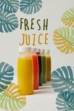 Organic detox smoothies in bottles standing in row, fresh juice inscription stock photos
