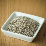 Organic Dry Chia Seeds in small white plate. Organic Dry Chia Seeds in plate on a table Royalty Free Stock Images