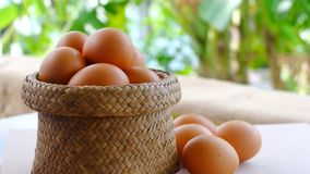 Organic eggs in a bamboo basket on a table. Royalty Free Stock Images