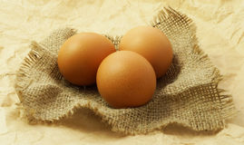 Organic eggs on sack and brown paper background. Selective focus Stock Photos