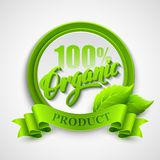 Organic emblem with ribbon and green leaves Stock Photos