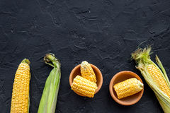 Organic farm food. Cutted corn cobs on black stone background top view copyspace Royalty Free Stock Photo