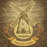 Organic farm poster with vintage windmill on the background texture of wooden boards. Retro hand drawn vector illustration label in sketch style Stock Images