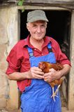 Happy farmer. Organic farmer holding chicken under his arms Royalty Free Stock Image