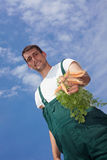 Organic farmer offering carrots Stock Photo