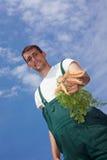 Organic farmer offering carrots Stock Photo