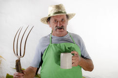 Organic farmer with a pitchfork and a beer mug Royalty Free Stock Photo