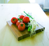 Organic food. Tomatoes,spring onion,cucumber, on wooden plate Stock Photos