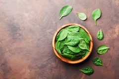 Organic food. Baby spinach leaves in wooden bowl on rustic stone table top view. Copy space for text. Stock Image