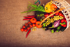 Organic food background vegetables and fruits in the basket. Fresh vegetables, fruits and lettuce in wicker basket. Warm toned. Horizontal Stock Photos