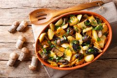 Organic food: baked wild mushrooms with potatoes, dill, parsley. And cheddar cheese in a baking dish close-up on the table. horizontal top view from above royalty free stock image