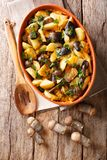 Organic food: baked wild mushrooms with potatoes, dill, parsley. And cheddar cheese in a baking dish close-up on the table. Vertical top view from above royalty free stock image