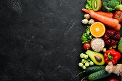 Organic food on a black stone background. Vegetables and fruits. Top view. Free copy space stock photos