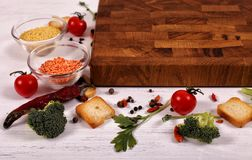 Organic food with empty brown cutting board on white wooden table. royalty free stock photo