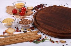 Organic food with empty brown round cutting board on white wooden table. stock photos