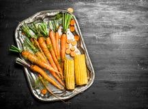 Organic food. Fresh carrots on a steel tray. On the black chalkboard Stock Photos