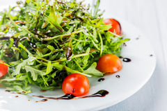 Organic food. Fresh salad of cherry tomatoes, lettuce, beniseed and sauce on a white plate close up Stock Image