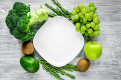 Organic food for homemade salad with green vegetables and plate gray desk background top view mock-up. Organic food for homemade salad with green vegetables and Stock Photos