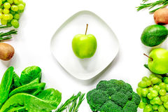 Organic food for homemade salad with green vegetables and plate white desk background top view mock-up. Organic food for homemade salad with green vegetables and royalty free stock photos