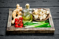 Organic food. Mushrooms with healthy vegetables in a wooden box. On a black rustic background royalty free stock photos