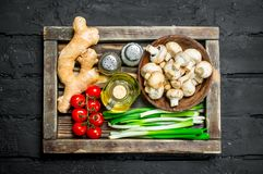 Organic food. Mushrooms with healthy vegetables in a wooden box. On a black rustic background stock photo