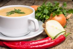 Organic food. Pea soup with diverse vegetables around on wood background Royalty Free Stock Images