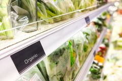 Organic food signage on modern supermarket vegetable aisle Stock Image