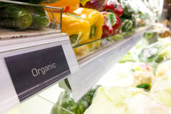 Organic food signage on modern supermarket vegetable aisle Stock Images
