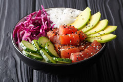 Organic food: tuna poke bowl with rice, fresh cucumbers, red cab. Bage and avocado close-up on the table. horizontal Stock Images