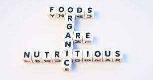 Organic foods. Concept ' organic foods are nutritious ' composed using uppercase black letters on white cubes , bright background Royalty Free Stock Images
