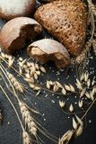 Organic fresh bread and wheat on a black background, vertical.  royalty free stock photography