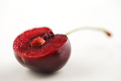 An organic fresh cherry halved and photographed in a creative manner Stock Images