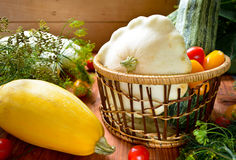 Organic fresh colorful raw vegetables in the basket. On wooden table Royalty Free Stock Photos