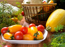 Organic fresh colorful raw vegetables in the basket. On wooden table Stock Images