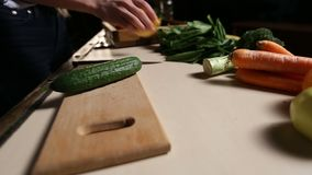Organic fresh cucumber on wooden chopping board. Organic fresh cucumber on wooden chopping board closeup. Female hand laying various ingredients out on the stock footage