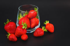 Organic fresh strawberries fruit in glass on black Royalty Free Stock Photos