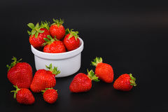Organic fresh strawberries fruit in white cup on black Royalty Free Stock Photography