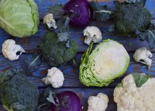 Organic fresh summer vegetables - different varieties of cabbages on wooden background. Cauliflower, kohlrabi, broccoli, white hea. D cabbage. Raw food Royalty Free Stock Photography