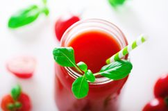 Organic fresh tomato juice in a glass jar, basil, cherry, salt, pepper and straw on light background. Clean eating and royalty free stock photography