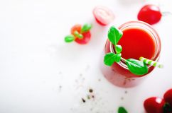 Organic fresh tomato juice in a glass jar, basil, cherry, salt, pepper and straw on light background. Clean eating and Stock Image