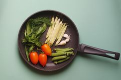Organic fresh vegetables courgette, tomato, asparagus, basil, dill, green peas, garlic in a frying pan royalty free stock photos