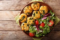 Organic fried meatballs with spinach and vegetable salad close-up. horizontal top view. Organic fried meatballs with spinach and vegetable salad close-up on a stock image