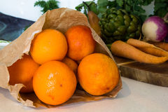 Organic fruit. (oranges) and vegetables surrounding a traditional wooden chopping board Royalty Free Stock Photography