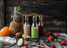 Organic fruit smoothies in glass bottles on wooden background royalty free stock image