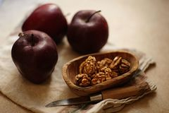 Organic fruits and nuts . Healthy snacks. Red apples and walnuts with napkin on a beige background . stock images